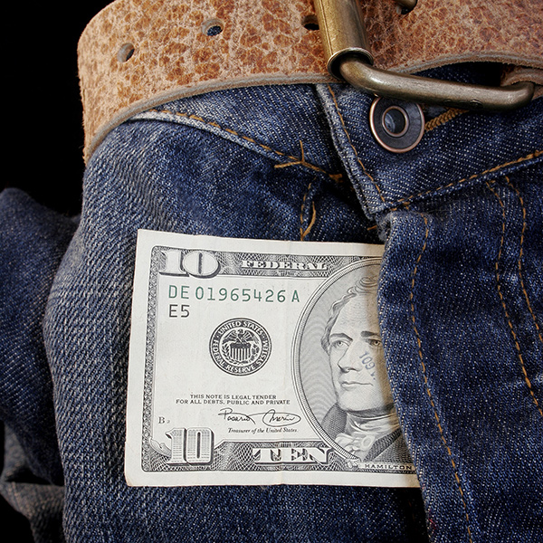 Ten dollar bill sticking out of crotch of blue jeans.